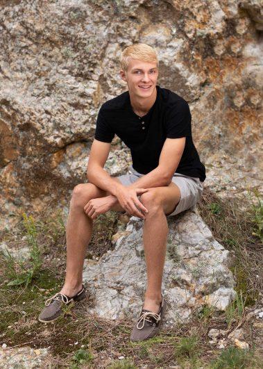 senior boy sitting on rocks