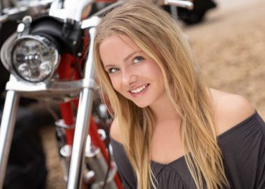 girl smiling with motorcycle in background
