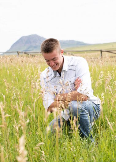 boy smiling in field of tall grass