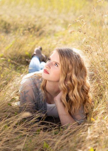 senior girl laying in field