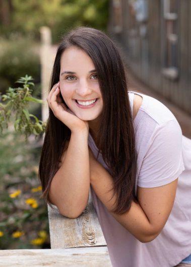 senior girl leaning on wooden fence