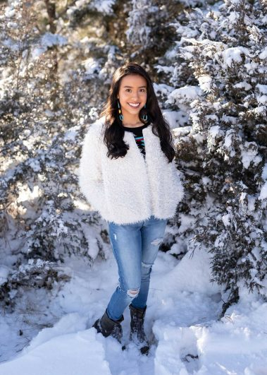 senior standing in snow