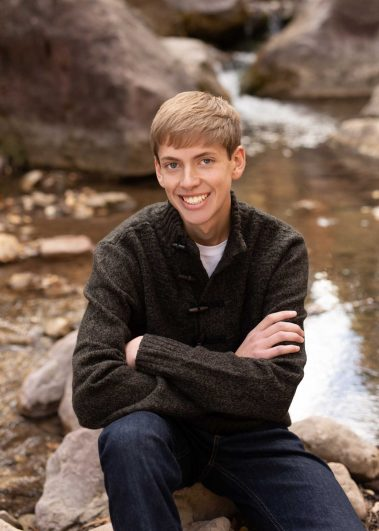 senior boy smiling on rocks