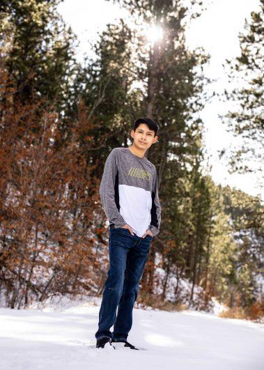 senior boy standing in snow