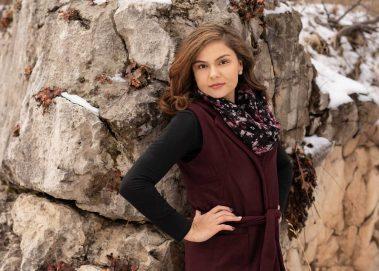 senior girl next to snowy rock