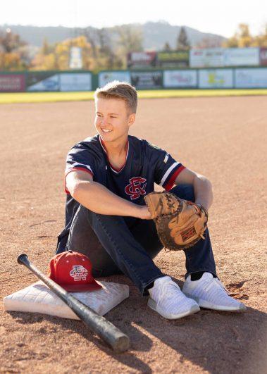 boy sitting next to baseball plate