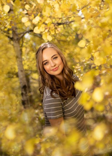senior girl with yellow leaves and trees