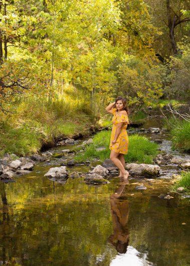 senior girl wading in water barefoot