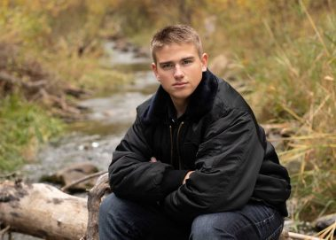 senior boy sitting on log