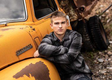 senior boy next to yellow truck