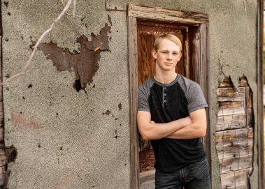 senior boy leaning against door
