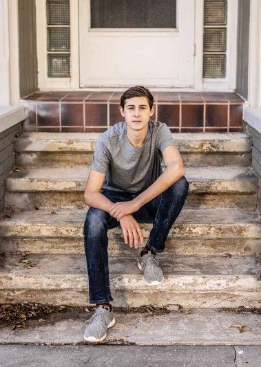 senior boy sitting on stone steps