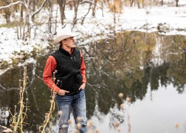 senior in cowboy hat near water
