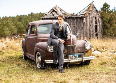 senior boy on hood of antique car