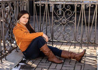 girl sitting next to metal railings
