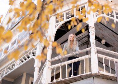 senior girl on 2nd floor porch