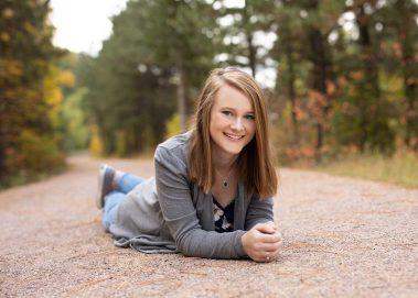 senior girl laying on path
