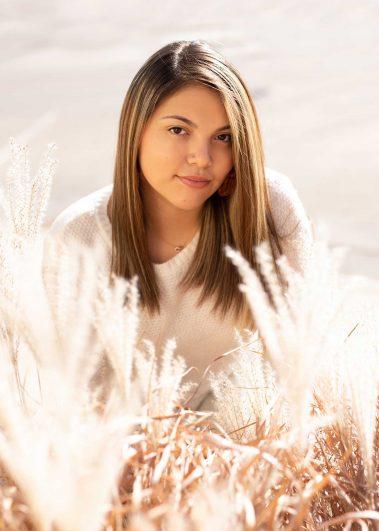 senior girl sitting in field