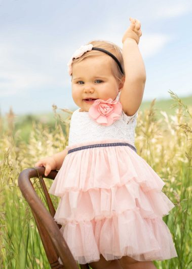 baby in field standing on chair