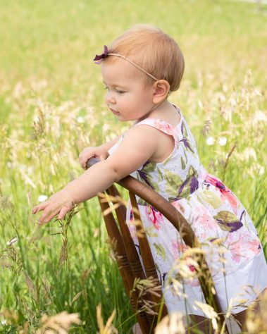 baby on chair touching wheat