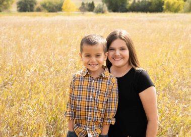 siblings smiling in field