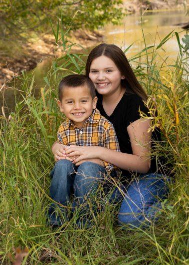 siblings smiling near creek