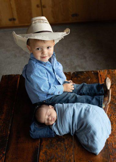little cowboy with newborn baby