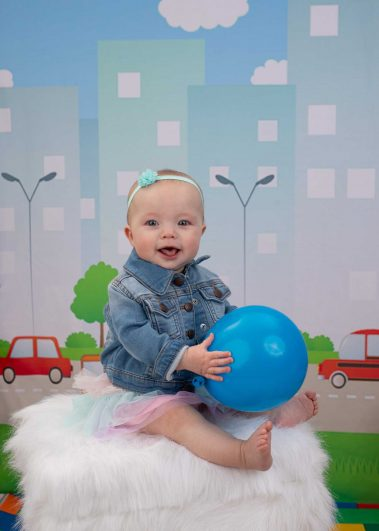 baby holding blue ball