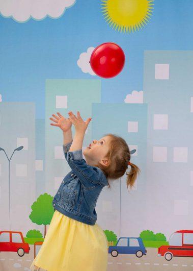 little girl tossing balloon