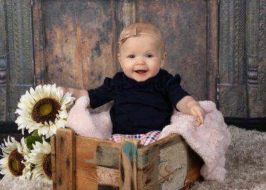 smiling baby girl in box