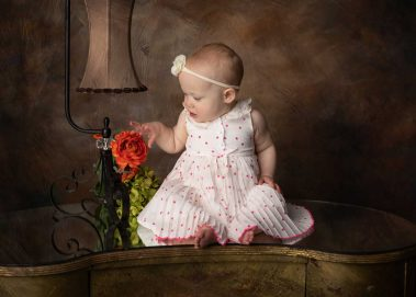 baby girl touching flower