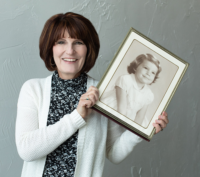 Linda Claussen holding her photo as a young child