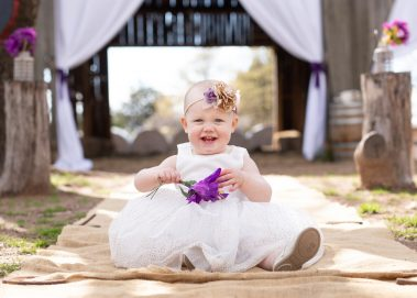 baby holding purple flower