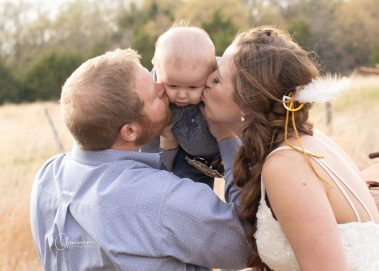 bride and groom kissing baby boy