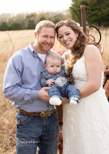 bride and groom holding baby