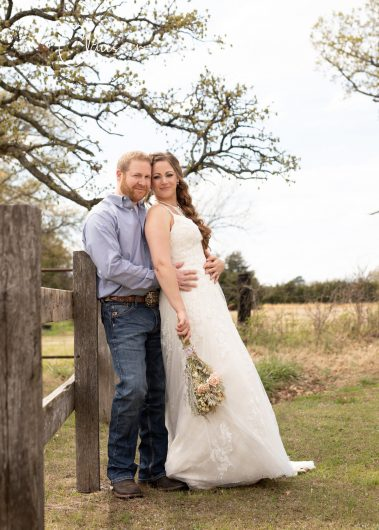bride and groom near wooden fence